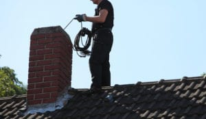 man inspecting chimney on roof