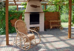 white concrete fireplace on patio with wooden rocking chair