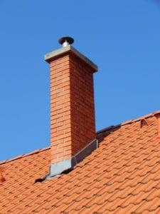masonry chimney on roof against blue sky